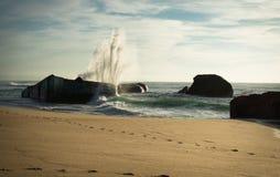 Huge wave water splash behind blockhouse on scenic beautiful sandy beach seascape with splashing waves Royalty Free Stock Photography