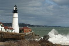 Huge Waves Break by Illuminated Portland Head Lighthouse in Main stock photography