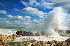 Huge waves breaking on rocks in sea. Summer huge waves breaking on rocks in the sea stock photos