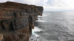 Huge waves crash against sea cliffs in Orkney, Scotland stock footage