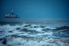 Huge waves in the deep sea water after sunset. Ca. Rgo ship sailing near the harbor Royalty Free Stock Photography