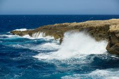 Wild waves of the ocean splash the dry shores of Gozo, Malta. Huge waves hit the rocky coastline of Gozo island Royalty Free Stock Image