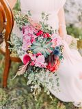 The huge wedding bouquet of colourful exotic flowers in the hands of the bride. Stock Photo