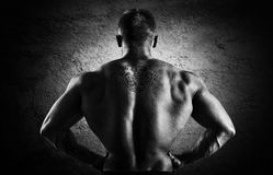 Huge weightlifter stands with his back to the camera and shows h. Is huge back. Back view Stock Photo