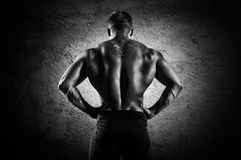 Huge weightlifter stands with his back to the camera and shows h royalty free stock photos