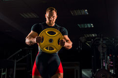 Huge weightlifter stands with a weight for the bar. In the gym Royalty Free Stock Image