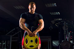 Huge weightlifter stands with a weight in his hands. In the gym Stock Photos