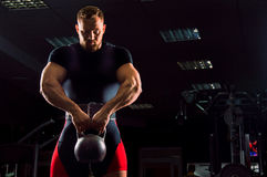 Huge weightlifter stands with a weight in his hands. In the gym stock photography