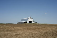Huge White Barn. Large white barn in a plowed field in spring royalty free stock images