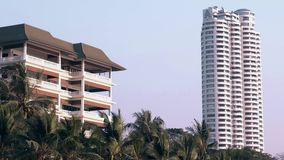 Huge white and brown modern hotel buildings under blue sky. With green palm leaves on foreground stock footage