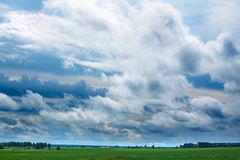 Huge white clouds in the blue sky above the green field stock photos