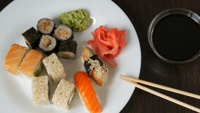 A huge white dish with a variety of sushi rolls from the national Japanese cuisine. Large white dish with a variety of sushi rolls from the national Japanese stock footage