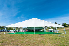 Huge white tent with green floor in field Stock Images