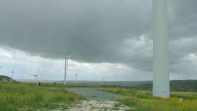 Huge wind turbine blades rotating under gray rainy sky, storm, vertical panorama. Stock footage stock footage