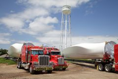Huge windmill vanes on trucks. Huge vanes for power-generating windmills sit on special trailers behind their semi-trucks under the water tower in Shamrock Royalty Free Stock Photography