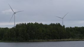 Huge windmills stand in the forest by the lake. New technologies. 4K Slow Mo