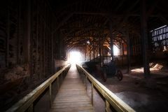 Wooden walkway in a large storage shed. A huge wood framed shed with a vintage metal tractor stored inside in a dusty abandoned factory Royalty Free Stock Photo