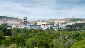A huge and working cement production plant production factory on mining quarry. Heavy indusrty with a lot of machinery. Chemical production and harm to royalty free stock photo