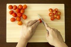 Hugga av Cherry Tomato på skärbräda Arkivbild