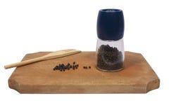 hugga av grinderpeppar för bräde Arkivfoton