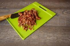 Huggen av bacon på en grön skärbräda med en förskärare Arkivbild