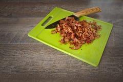 Huggen av bacon på en grön skärbräda med en förskärare Royaltyfri Fotografi