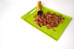 Huggen av bacon på en grön skärbräda med en förskärareisolator Arkivfoto