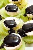 Huggen av banan som staplas på kiwi med chokladsås Royaltyfri Foto