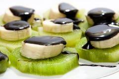 Huggen av banan som staplas på kiwi med chokladsås Royaltyfri Bild