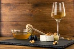 Huggen av camembertost, muttrar, honung och söta druvor på bakgrunden av ett exponeringsglas av vitt torrt vin fotografering för bildbyråer