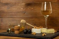 Huggen av camembertost, muttrar, honung, söta druvor och kork från vinflaskan på bakgrunden av ett exponeringsglas av vitt torrt  royaltyfria bilder