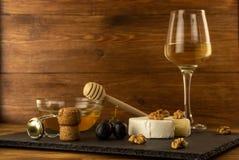 Huggen av camembertost, muttrar, honung, söta druvor och kork från vinflaskan på bakgrunden av ett exponeringsglas av vitt torrt  arkivbilder