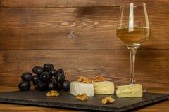 Huggen av camembertost, muttrar och söta druvor på bakgrunden av ett exponeringsglas av vitt torrt vin royaltyfri foto