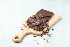 Huggen av choklad på skärbräda arkivfoton