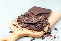 Huggen av chokladstång på skärbräda som stekhet ingrediensförberedelse royaltyfri bild