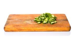 Huggen av grön Chili Peppers On Chopping Board dropp arkivfoton
