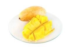 Huggen av gul saftig mogen frukt av den halva mango på tvären som ligger på exponeringsglaset på bakgrunden av en isolerad hel ma arkivfoton