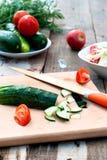 Huggen av gurka- och tomatsallad på en skärbräda Royaltyfri Fotografi