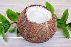 Huggen av kokosnöt på en trätabell Arkivfoto