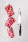 Huggen av rå grisköttfilé med köttkniven Arkivfoto