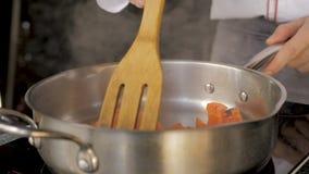 Huggen av tomat som steker i panna stock video