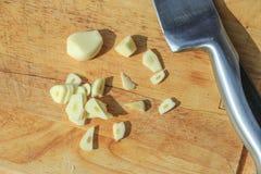 Huggen av vitlök med rostfritt stålkniven som är närliggande på en träskärbräda Detta var från en matlagningkurs som jag tog var  Fotografering för Bildbyråer