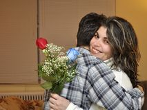 Hspanic Teenager Hugging His Mother. A teen gives a two roses and hugs her mom in during Mothers Day. Latin family showing love and affection for each other Stock Photo