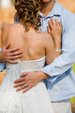 Hugging the bride. A vertical photo of a caucasian couple holding each other on their wedding day Stock Photo