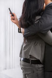 Hugging business couple yet still using phone royalty free stock image