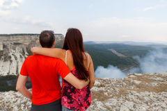 Hugging couple backdrop of mountains Royalty Free Stock Photo