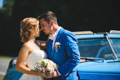 Hugging Couple at Blue Cabriolet. Hugging couple with bouquet at blue cabriolet Stock Photo