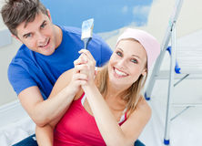 Hugging couple having fun while painting a room Royalty Free Stock Images