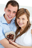 Hugging couple holding chocolate and smiling Stock Photo