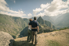 Hugging couple looking at Machu Picchu, Peru, toned image. Hugging couple standing in contemplation on the terraces above Machu Picchu, the most visited travel Royalty Free Stock Photography